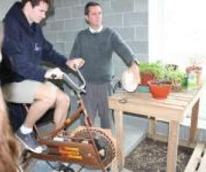 Lonnie Gamble, director of the Sustainable Living Center, demonstrates electricity generation using a bicycle powered by Summer Fitzpatrick-Keith '16