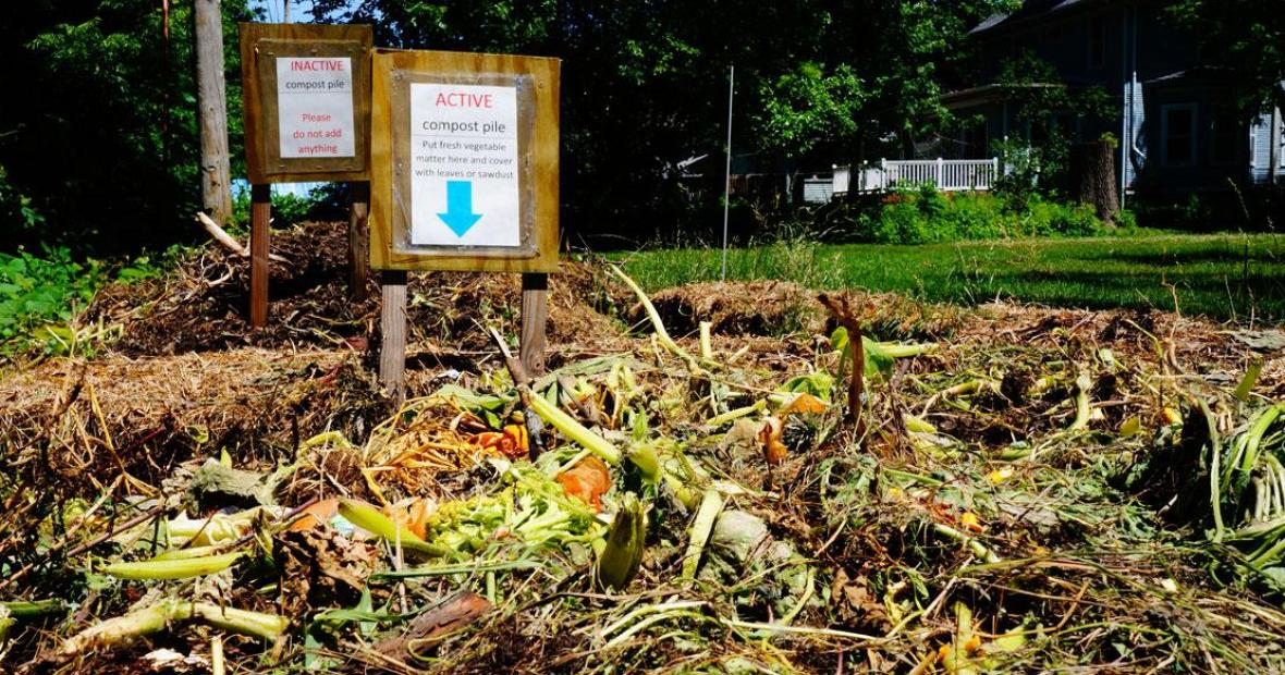 Fresh plant debris in the active compost pile with inactive pile in back. Signs instruct workers on adding debris to active pile and covering with leaves or sawdust.