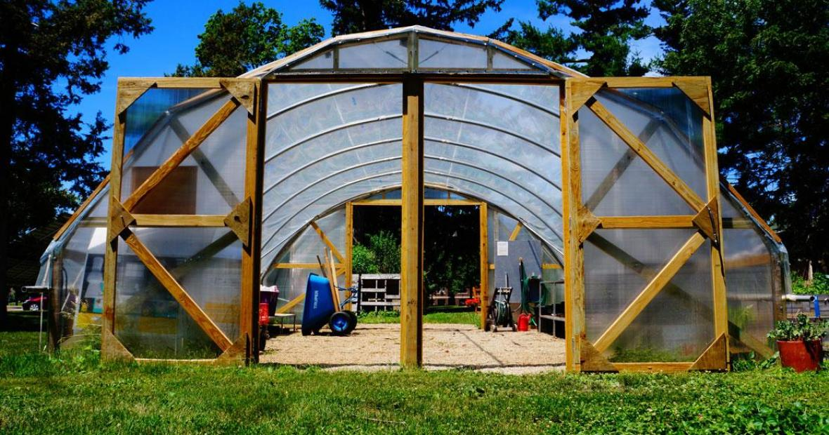 View through the hoop house doors shows stored wheelbarrow, equipment inside