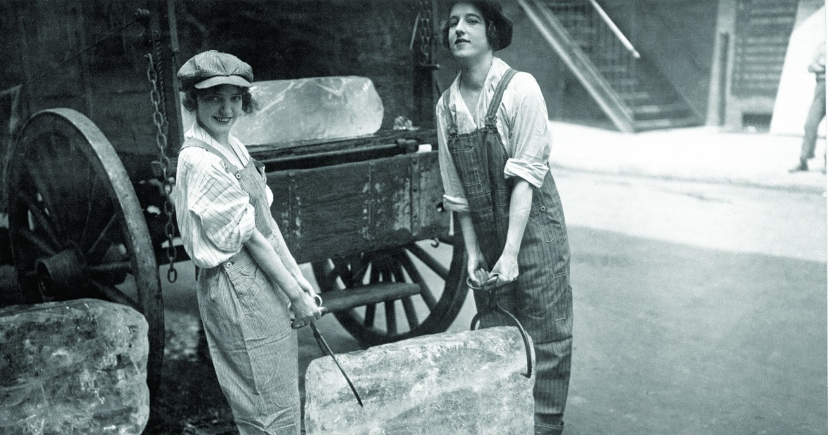 Two young women carry a large block of ice between them with large tongs