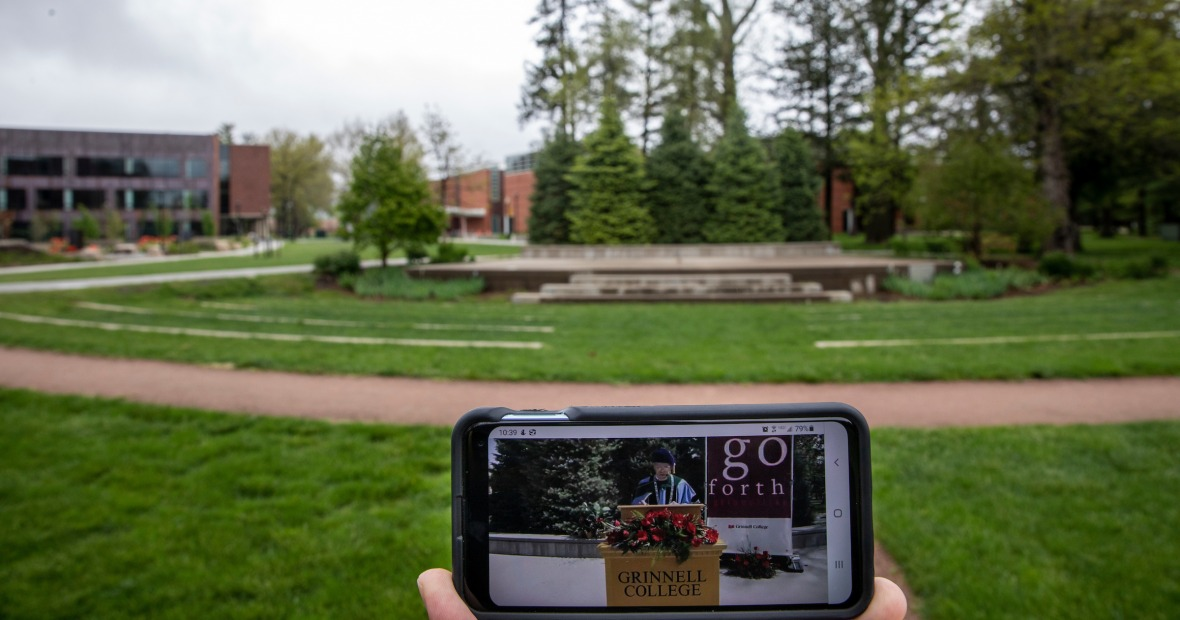 Smart phone in foreground showing virtual commencement in front of empty outdoor commencement stage in background