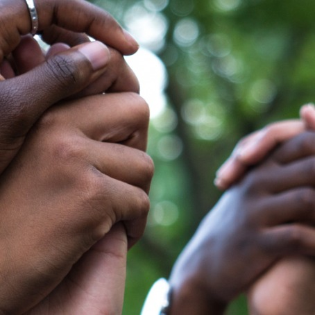 Close-up of Black people's raised, clasped hands