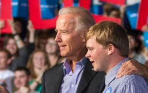 Biden and student at lectern with crowd behind them