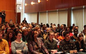 Speaker in Rosenfield Center Room 101 talks to packed crowd