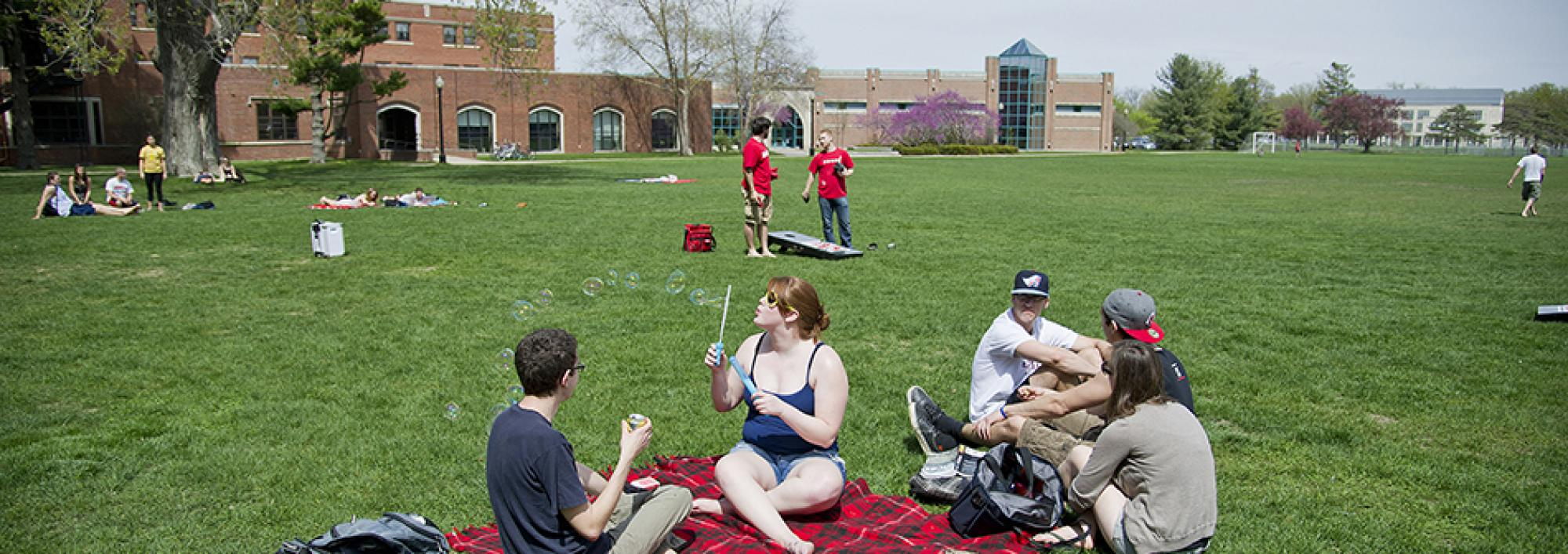 Students blow bubbles and play games on Mac Field