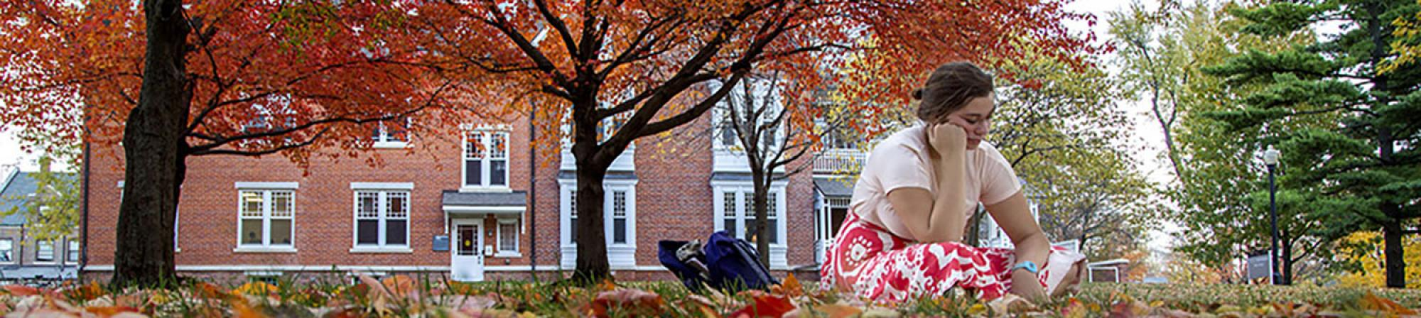 Student studies outdoors on a colorful fall day