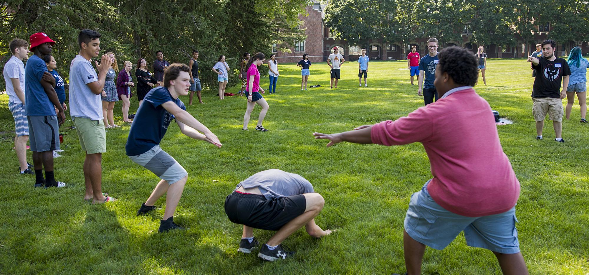 Large circle of students playing an active game on the grass.