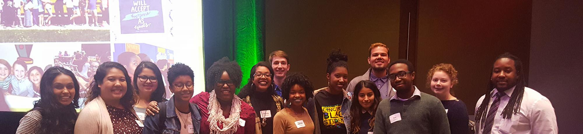 A group of students pose for a photo with a presentation screen behind them for Angela Davis