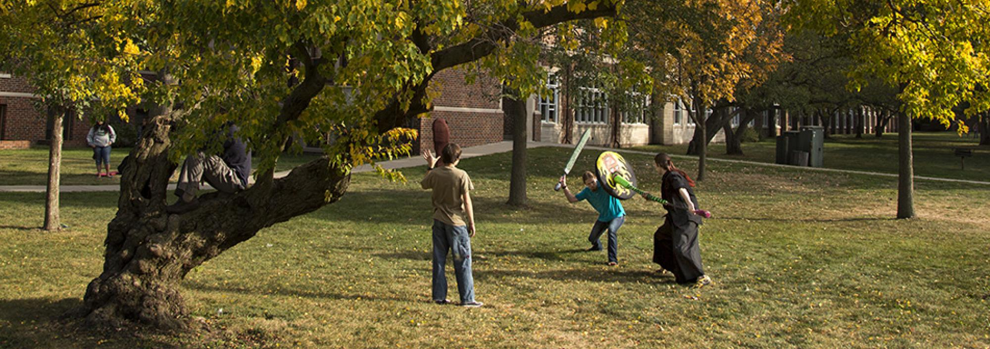 Students under the trees fight with foam weapons and shields