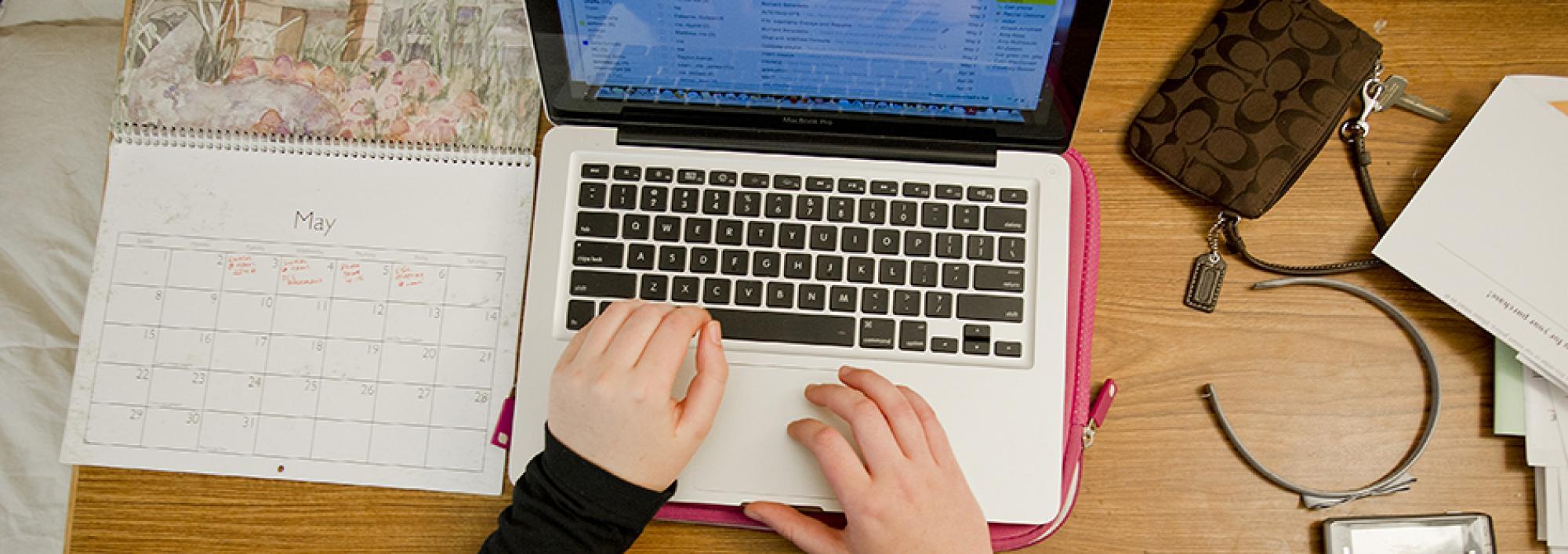 Hands on an open laptop