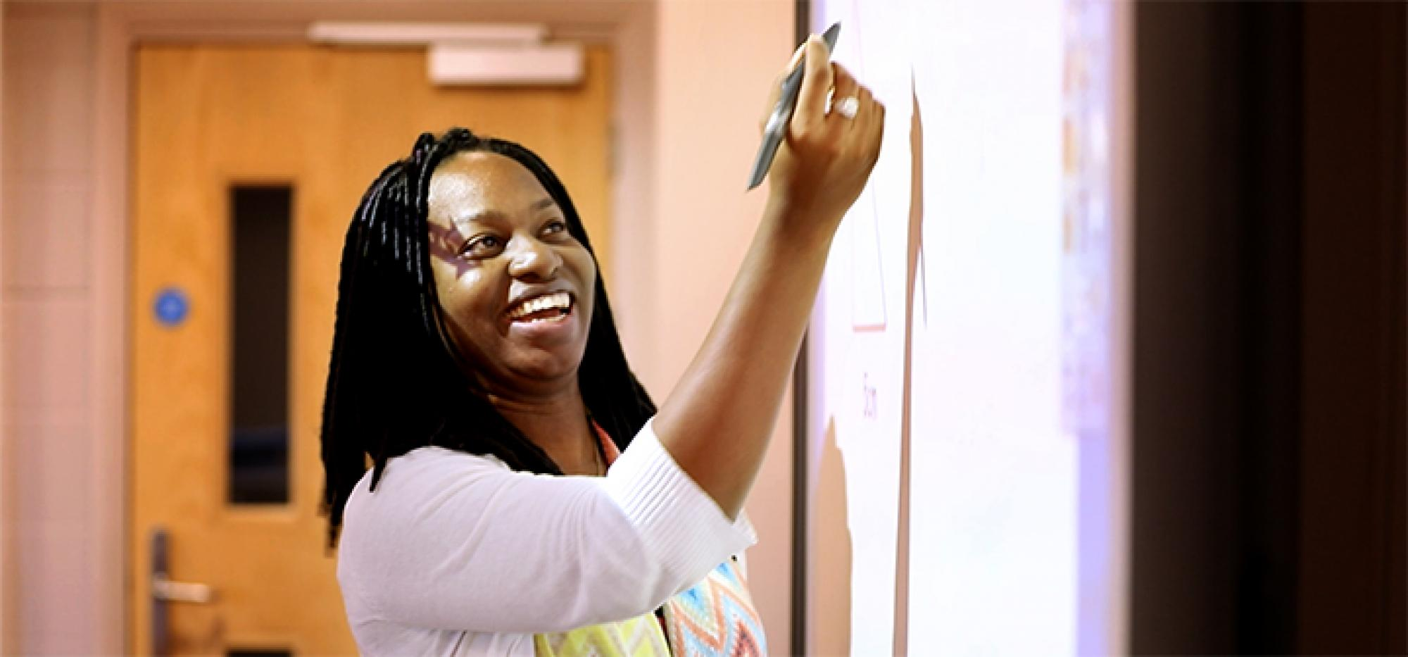 Kaydi-Ann Newsome writes at a marker board
