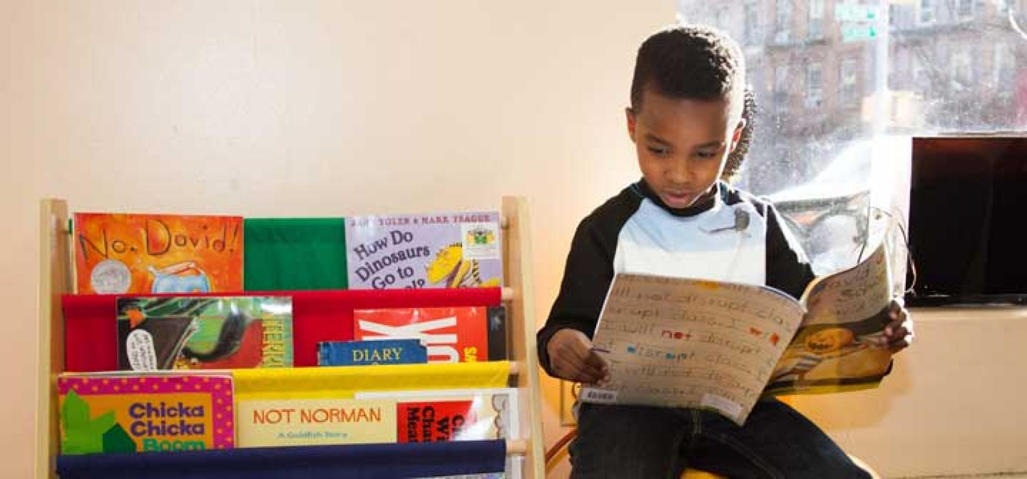 Young boy reads at a Barbershop Books station