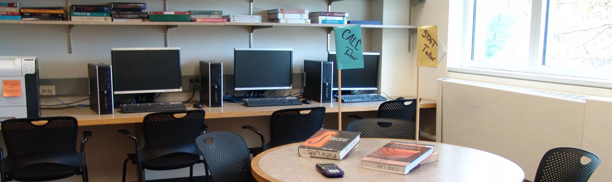 Part of the Math Lab showing a small group table with textbooks and a calculator, some computers, and the flags identifying the current Math tutor and Stats tutor.