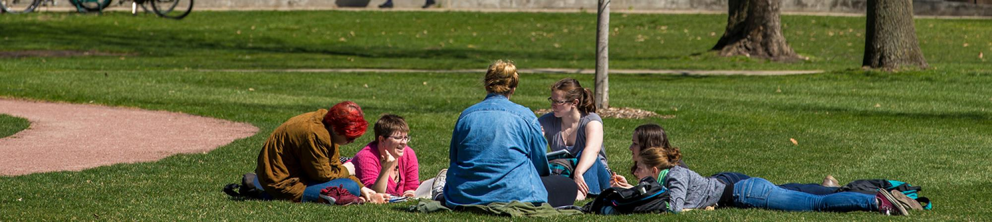 fice students sitting and hanging out on mac field in a circle