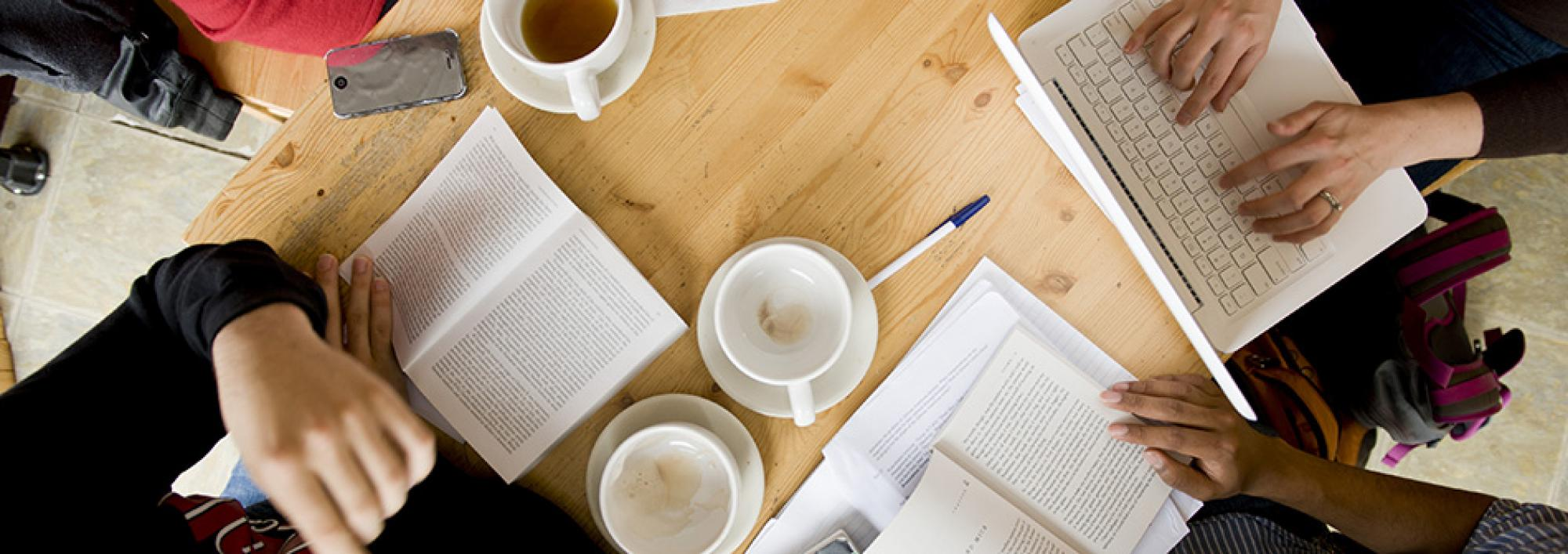 Coffee cups, books, pens, and paper are strewn around a table