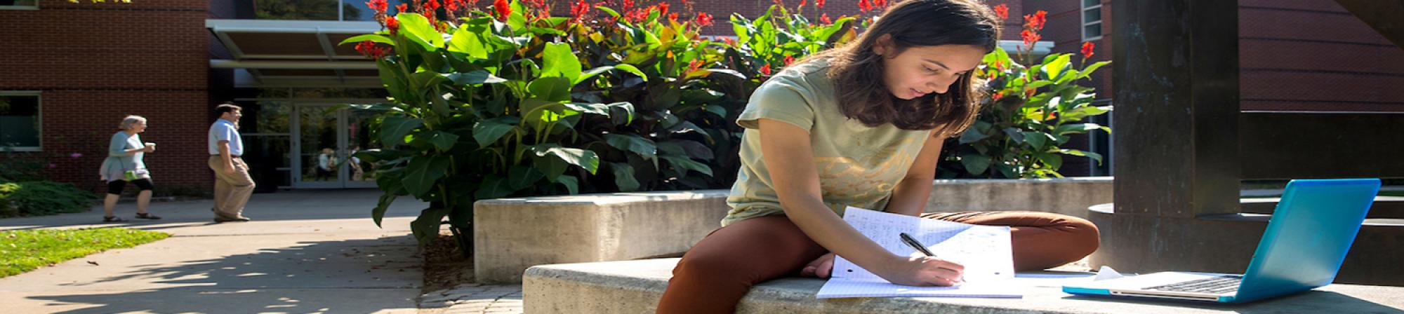 female student studing outside on a bench with her laptop on a sunny day