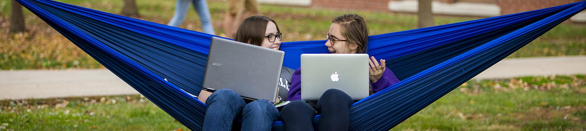 Two students sit in an outdoor hammock with their laptops