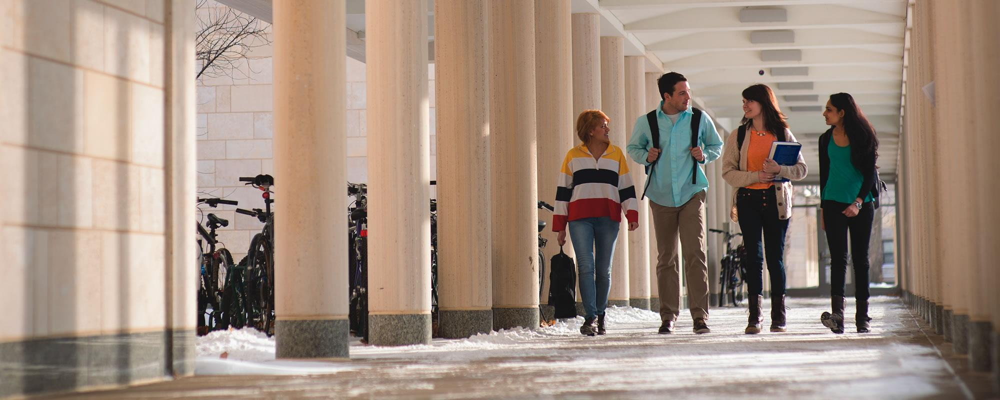 Four students walk through East Campus loggia