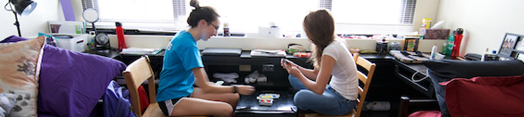 two female students sitting in their room playing cards and using the mini-fridge as a table