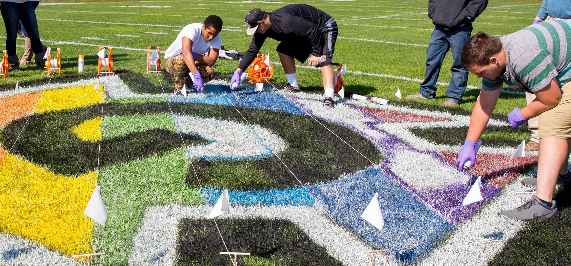 Students and staff paint a rainbow-striped Honor G on the center of the football field