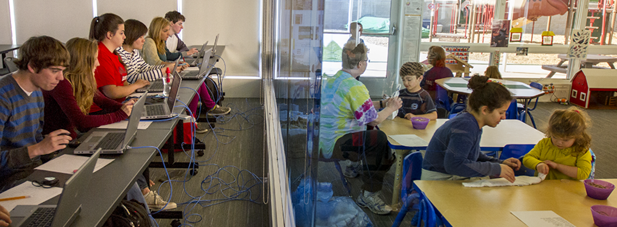Psychology students observe children through a one-way glass at the Grinnell College Preschool