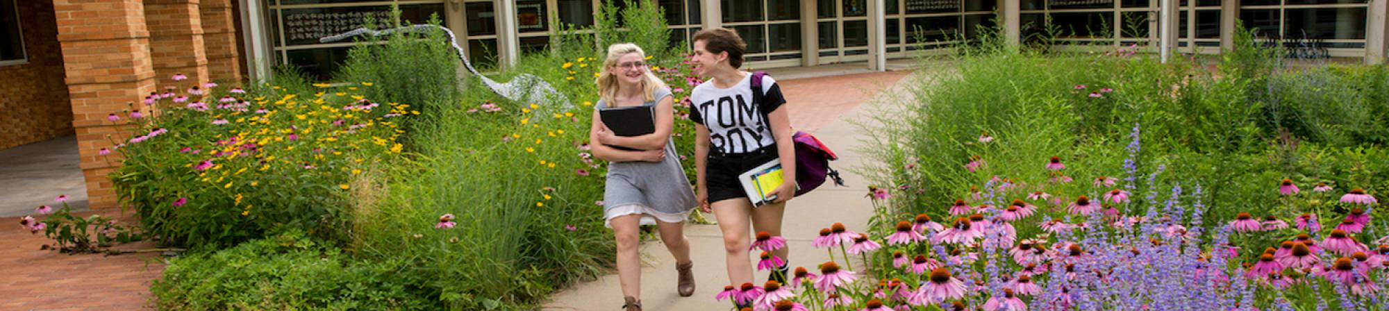 two female students walking out of an academic building on a sidewalk with wild flowers on both sides of them