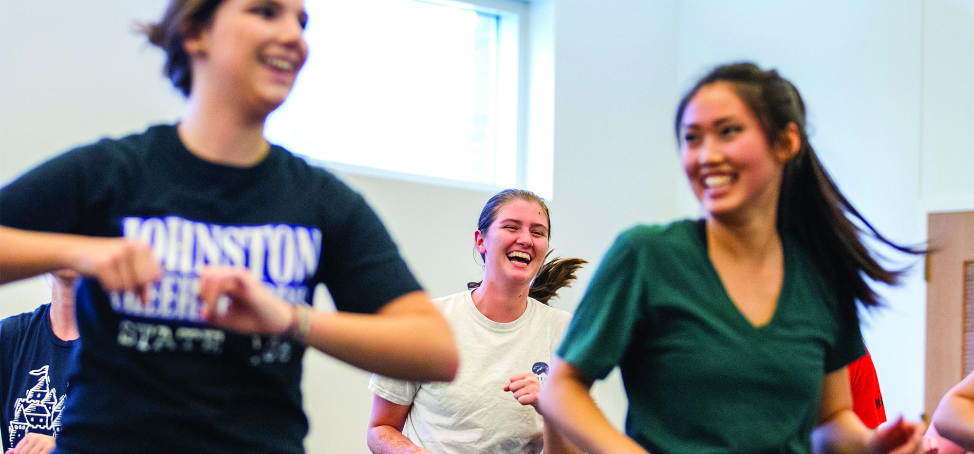 Students laugh while taking a zumba class