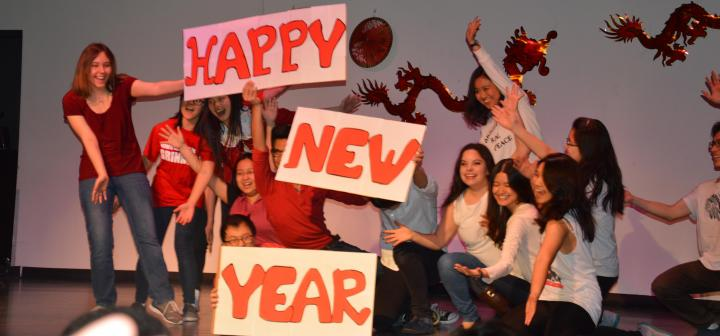 Students holding signs that say Happy, New, & Year