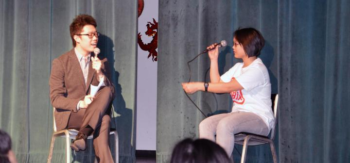 Two seated people talking on microphones