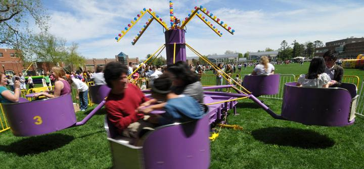 students on carnival ride with spinning arms holding spinning cars
