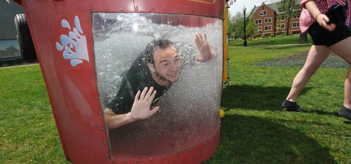 dunked man peers out the window of the water-filled dunk tank