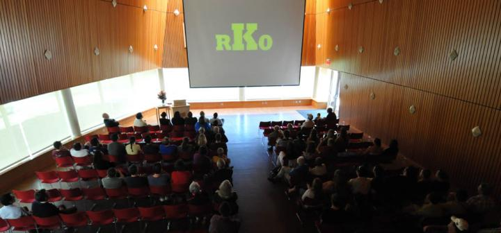 Audience beginning to fill large room, with screen displaying RKO in large letters at front