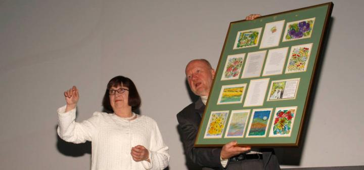 Woman standing next to a man holding a large framed board with cards