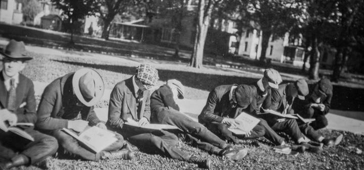 Men in caps sitting on grass reading