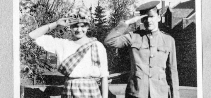 woman and man in uniforms salute the camera, with south campus dorms and trees in the background