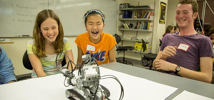 Two girls laugh at small robot as college student looks on