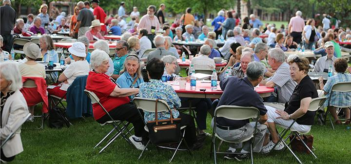 Reunion attendees of all ages share an outdoor picnic