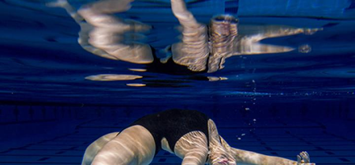 Swimmer performing move in a pool is mirrored by the pool's surface above.