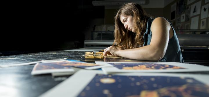 Student sits at table covered with artwork and carves