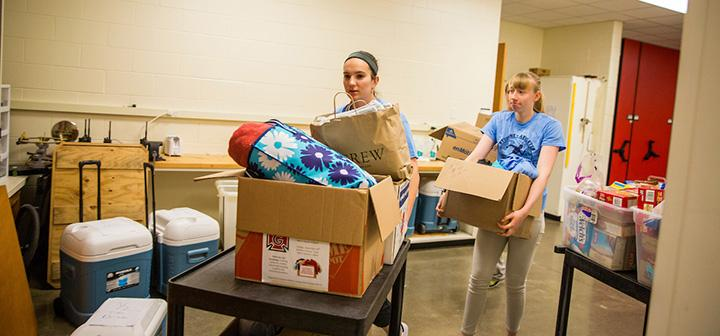 Two students load a cart with donations for hurricane relief