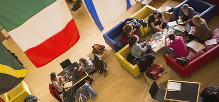 Students in comfy chairs underneath large flags.