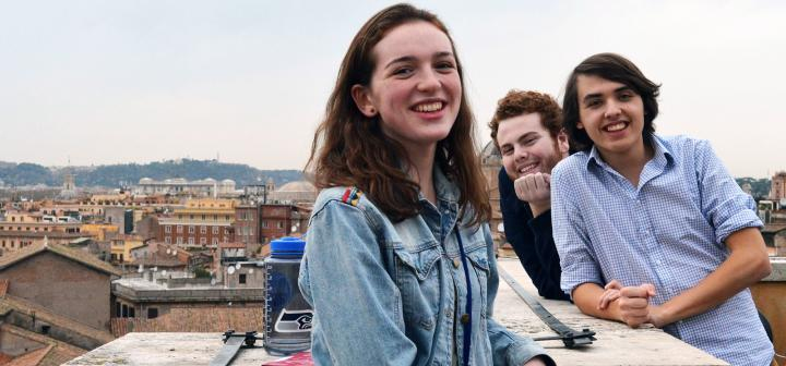 Students relax on a rooftop with the city visible behind them.