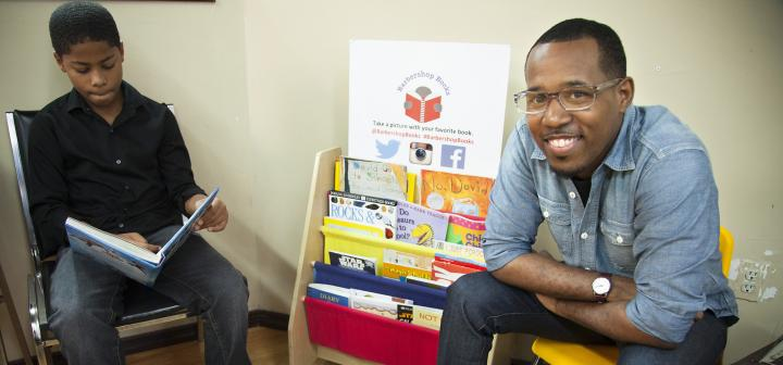 Boy reading and man looking at camera, both flanking a small display of books