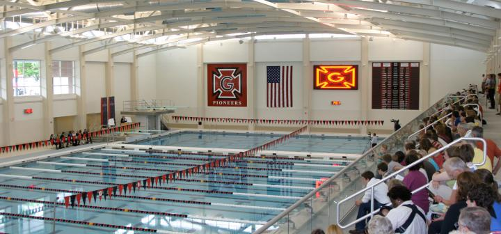 Crowd and speakers flank pool during dedication ceremony