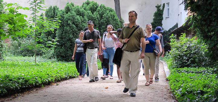 Students and professors walk path through the overgrown cemetery