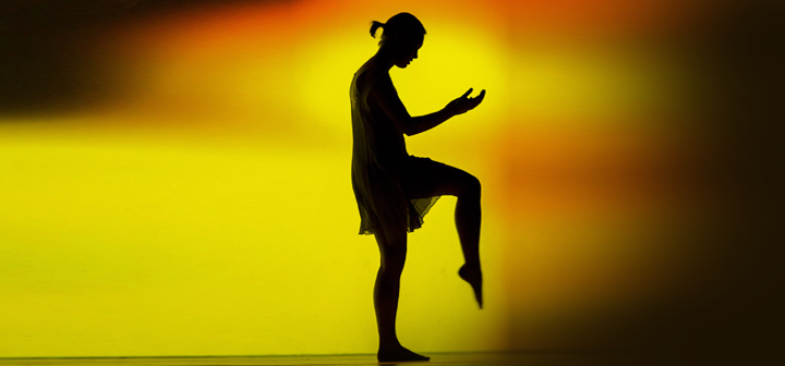 Silhouette of a dancer against a yellow and orange lit backdrop