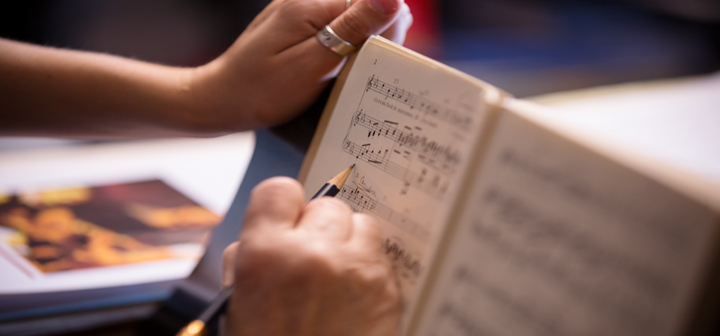 Close up of person writing on a musical score