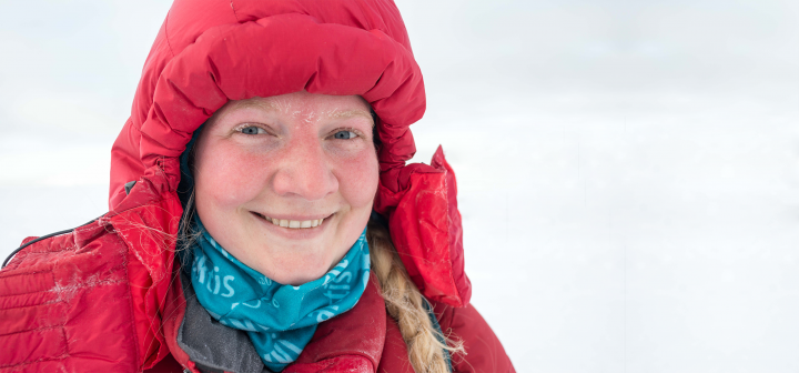 Smiling woman with snow on her eyelashes and brows, in a puffy red parka