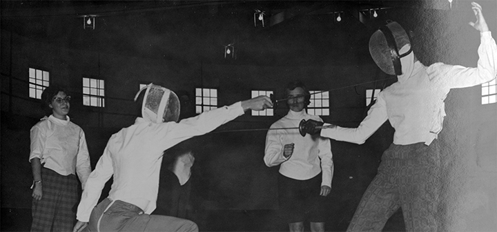 Fencers face off with spectators in background