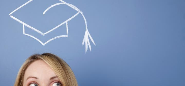College Girl stands in front of a chalkboard with mortar board drawn above her head
